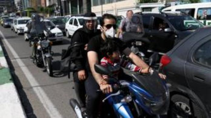 Iranian family on a motorcycle in a street in Tehran