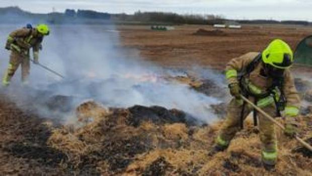 Two firefighters prodding burning hay with a long stick