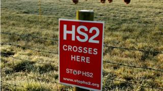 A poster protesting against a proposed high speed rail project linking London with northern England (HS2) is nailed to a fence on a field near Lymm, northern England