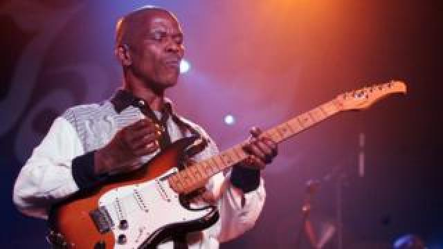 Ray Phiri performs on stage with his guitar
