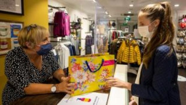 Mary Rogan, shop assistant at Joules in Belfast, hands Ella Copper her purchase while wearing a face mask as face coverings are now compulsory for shoppers in Northern Ireland