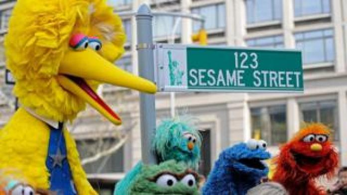 Big Bird (L) and other puppet characters from Sesame Street pose next to the temporary road sign on November 9, 2009