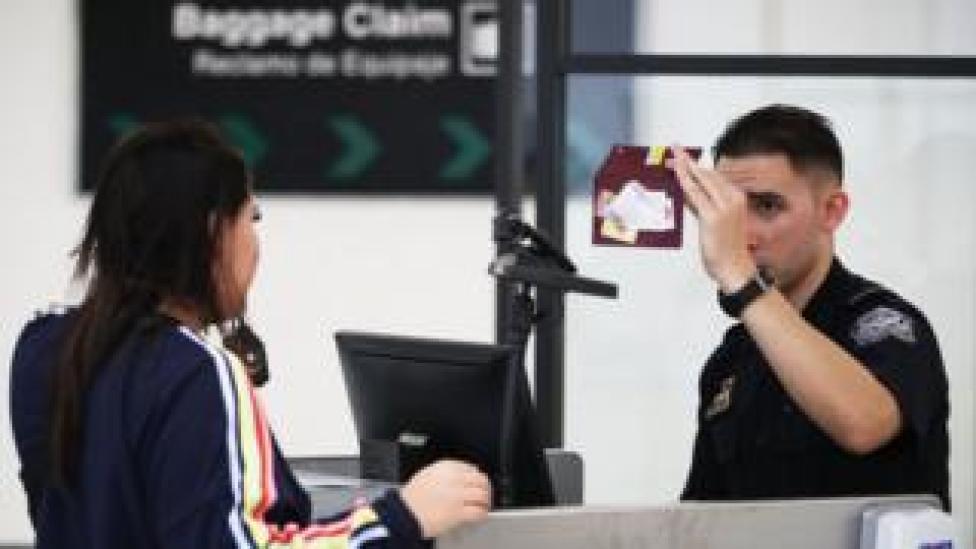 Una mujer en un punto de control de extranjería en un aeropuerto de Estados Unidos.