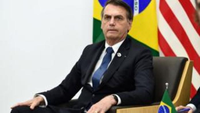 Bolsonaro sentado em cadeira com bandeiras do Brasil e de outro país atrás
