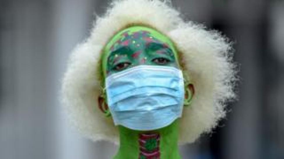 A Tanzanian performance artist t Alex Kalemera dressed up in a mask
