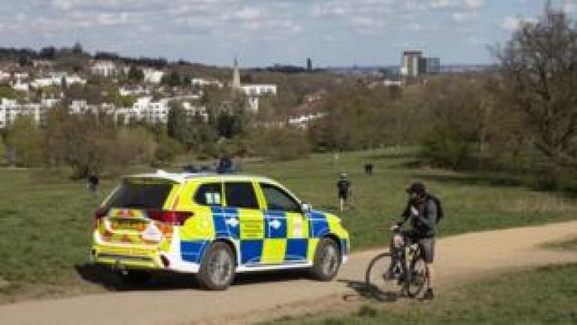A man is told by a police officer that there is no cycling at Parliament Hill Viewpoint in Hampstead Heath on April 04, 2020 in London, England.