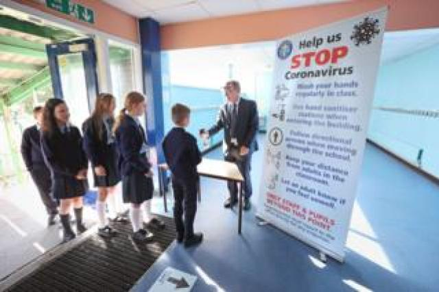 Chris Donnelly, principal of St John The Baptist Primary School in West Belfast uses sanitizer on pupils' hands, as schools in Northern Ireland reopen to pupils following the coronavirus lockdown on 24 August 2020