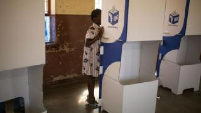 A girl watches while her mother marks her ballot at at a polling station at the Sheshego township, on the outskirts of Polokwane on May 8, 2019.