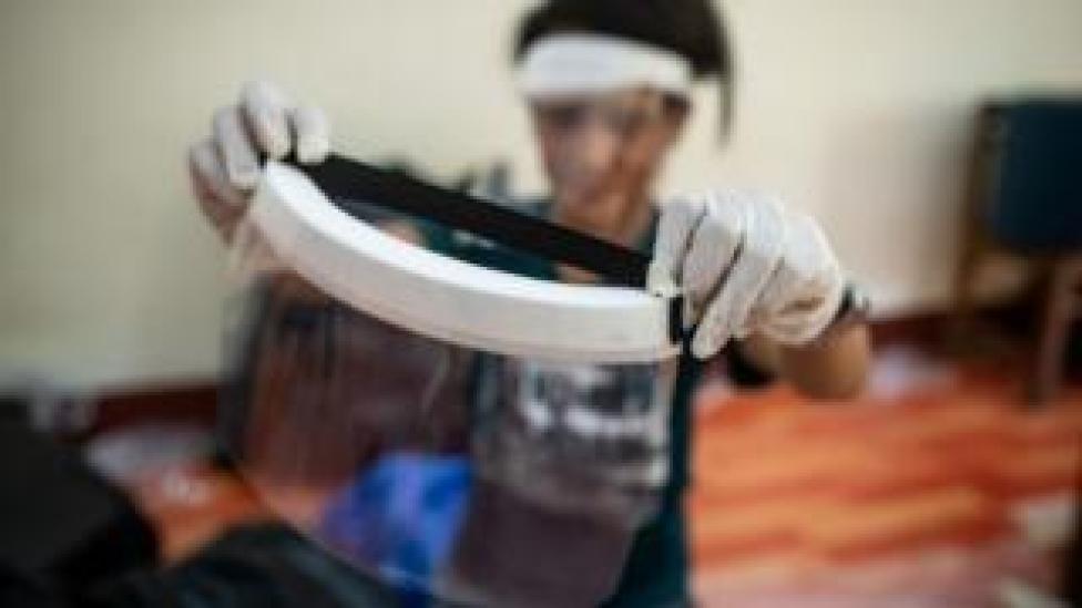 طالب طب يتفحص درع الوجه اليدوي قبل تسليمه للأطباء والممرضات في يانغون، ميانمار.