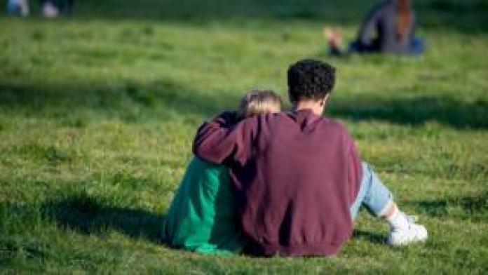 People sitting in the sun on Primrose Hill in London