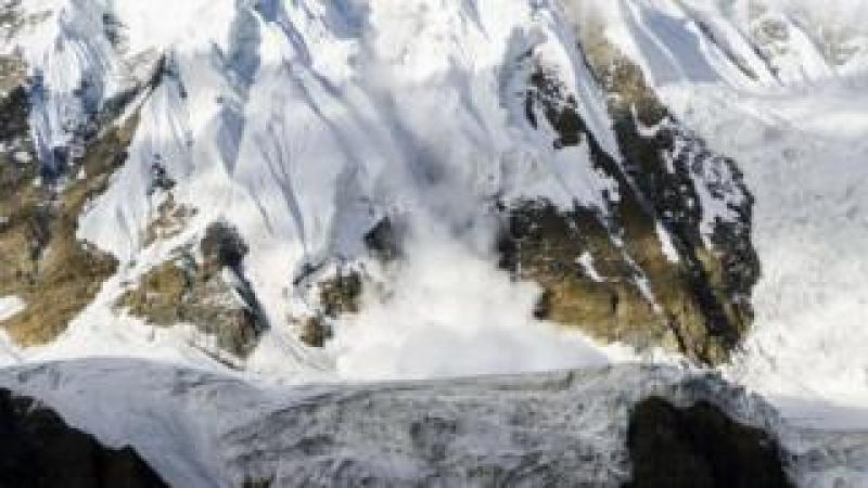 An ice avalanche is shooting down an icy rock slope