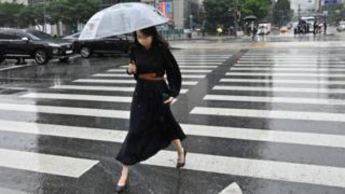 A woman holding an umbrella crosses a road in central Seoul, South Korea.