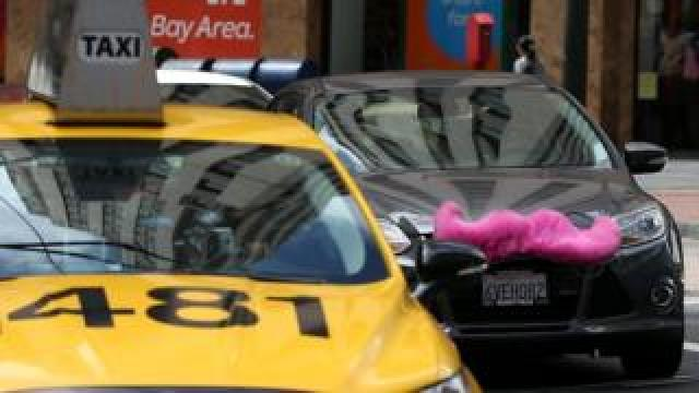 A Lyft car drives next to a taxi on June 12, 2014 in San Francisco, California.
