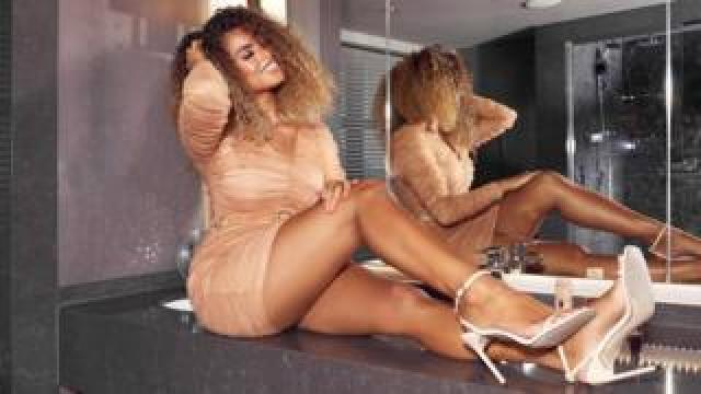 Queen of the Island Amber Gill models her collection with Boohoo-owned MissPap in a tan mini dress in a monochrome bathroom
