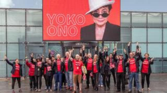 MIF volunteers in front of a screen showing Yoko Ono