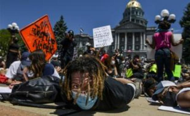 Thousands of people staged a die-in demonstration next to the Colorado State Capitol with their hands behind their backs to protest the death of George Floyd in Denver, Colorado, 30 May 2020