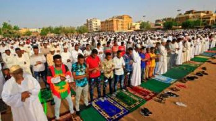 """Muslim worshippers gather for the prayers of Eid al-Fitr, the Muslim holiday which starts at the conclusion of the holy fasting month of Ramadan, in the district of Jureif Gharb of Sudan""""s capital Khartoum early on May 24, 2020, despite government regulations banning congregations due to the COVID-19 coronavirus pandemic."""