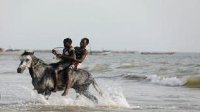 Men ride a horse in the sea in Senegal