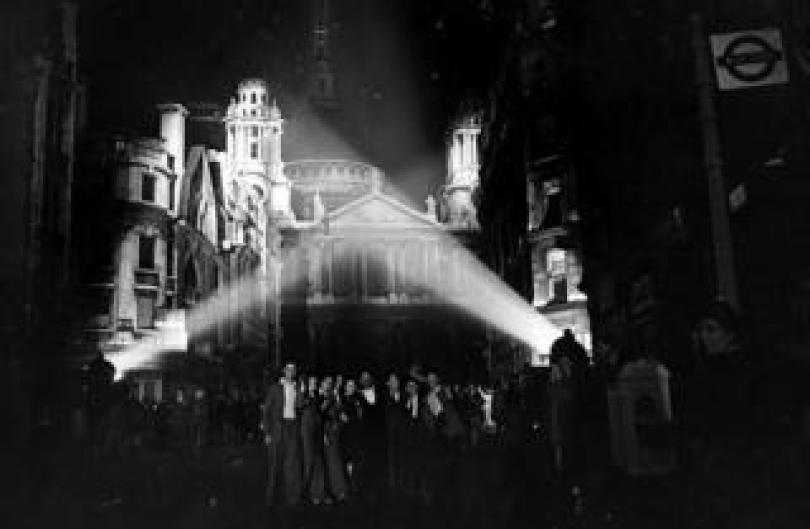Floodlights illuminate the building tops near St Paul's Cathedral with revellers on the street
