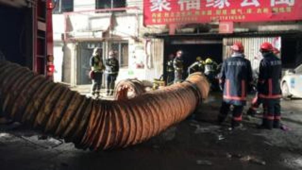 Firefighters work at the site of a house fire, in Daxing district, Beijing, China (19 November 2017)