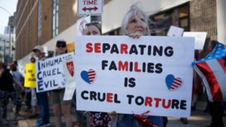 """A woman holds a sign saying """"separating families is cruel torture"""""""