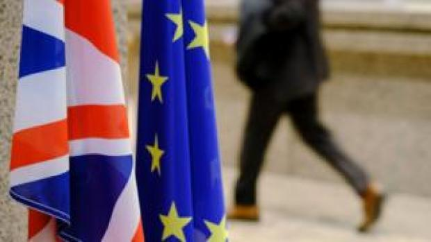 Man rushes by UK and EU flags