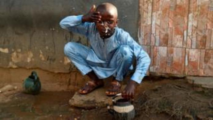 A boy performs the ritual ablutions before praying at a mosque to celebrate Eid al-Fitr at a mosque in Kara Ibafo in Ogun State, on May 24, 2020.