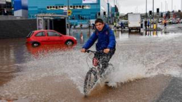 Boy cycles through flood water near stranded car