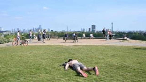 A man sunbathes on Primrose Hill in London on May 7, 2020 as life continues in Britain under a nationwise lockdown to slow the spread of the novel coronavirus