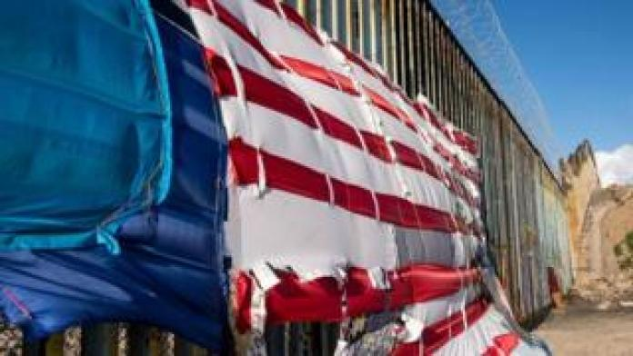 A patchwork representing a US flag hangs on the US-Mexico border in Playas de Tijuana, Baja California State, Mexico, on March 8, 2019