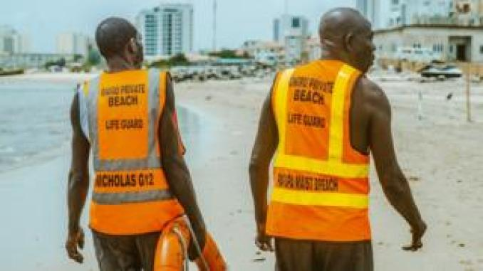 Two lifeguards walk on the beach in Lagos, Nigeria