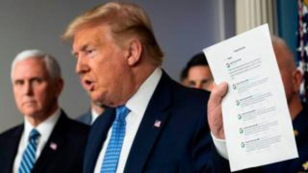 Donald Trump holding up printed sheet of Google tweets