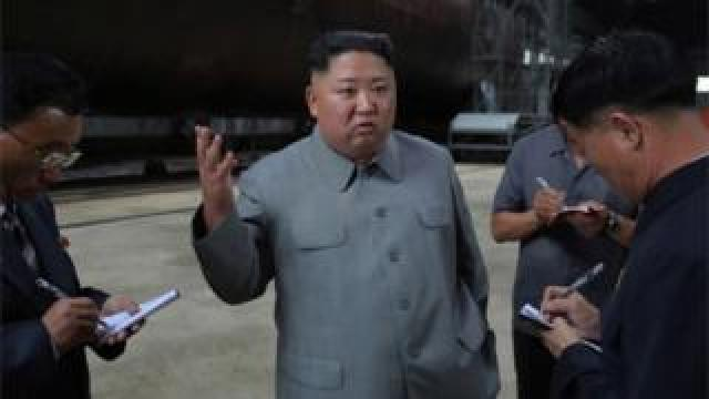 A photo released by the official North Korean Central News Agency (KCNA) on 23 July 2019 shows Kim Jong-Un (C), speaking to officials after making a round of the newly-laid down submarine at an undisclosed location in North Korea.