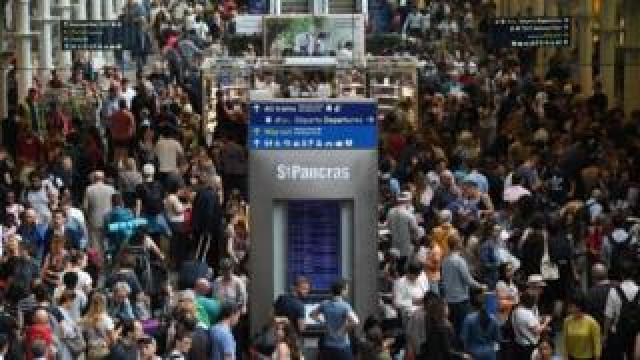 Passengers wait for trains at St Pancras International station in London