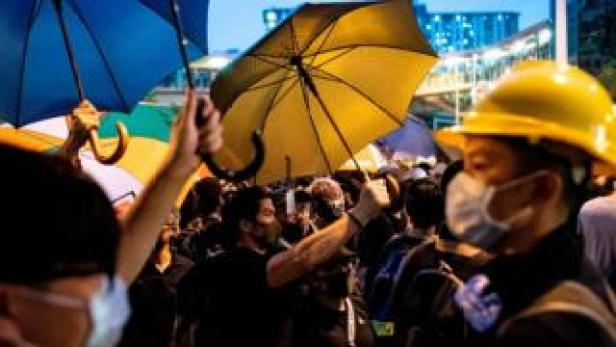 Hong Kong protesters clutch yellow umbrellas