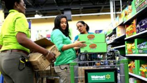 Walmart staff stock shelves in the supermarket
