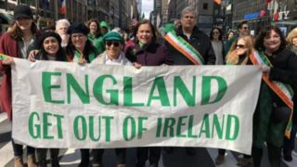 Mary Lou McDonald marching with banner