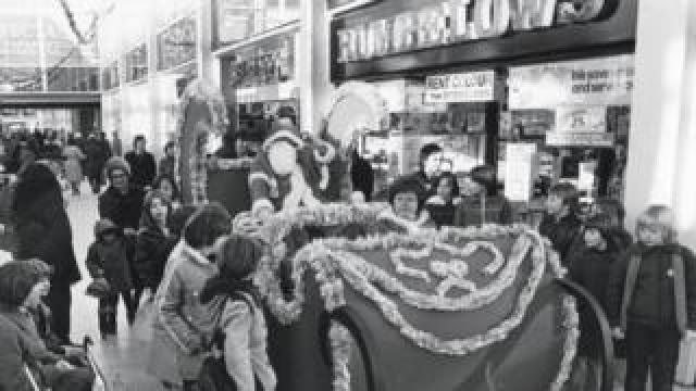 Father Christmas on his sleigh going through the shopping centre
