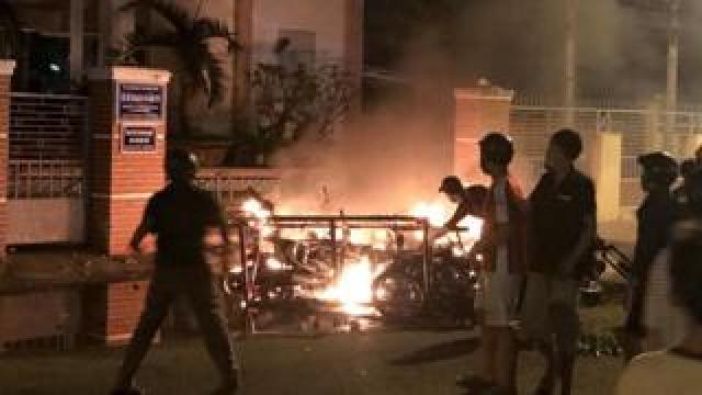 Protesters burn motorcycles in front of a provincial office in Vietnam's coastal Binh Thuan province