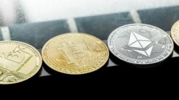 Physical coins representing various digital currencies