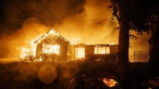 A home burns after winds push the Hillside fire down a hill to engulf homes in San Bernardino