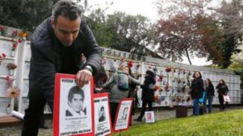 "A man places a poster of a person who went missing during former General Augusto Pinochet's regime, that reads ""Political executed"", during a rally marking the anniversary of the 1973 military coup in Santiago, Chile September 10, 2017"