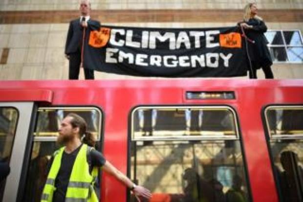 Activists on to a Docklands Light Railway train at Canary Wharf