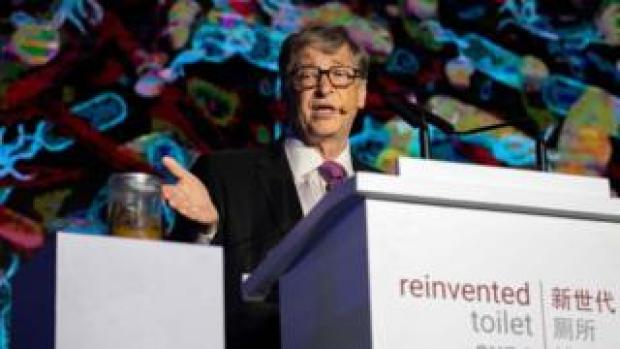 Bill Gates motions toward a jar of human faeces on stage