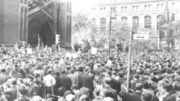 A noontime crowd at Trinity Church on Lower Broadway gather as part of the national Moratorium to End the War in Vietnam (Moratorium Day) demonstration. October 15, 1969