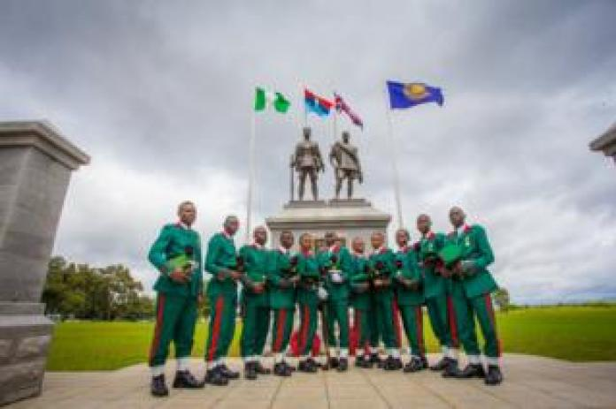 Soldiers and soldiers in green and red uniforms stand in front of the memorial with flags and two statues in Abuja.