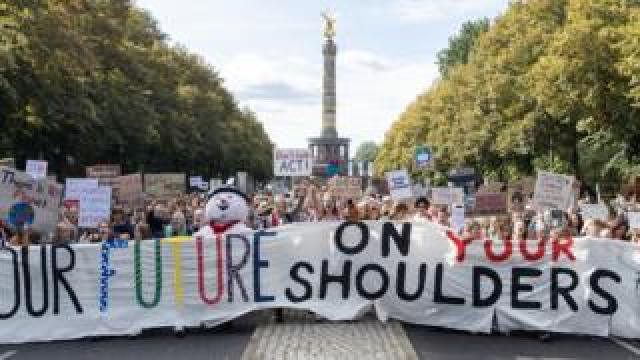 "Protesters with a banner ""Our future on your shoulders"" attend a demonstration at the Victory Column"
