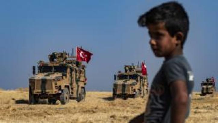File photo showing a Syrian boy watching Turkish military vehicles taking part in a joint patrol with US forces near Tal Abyad, Syria (4 October 2019)
