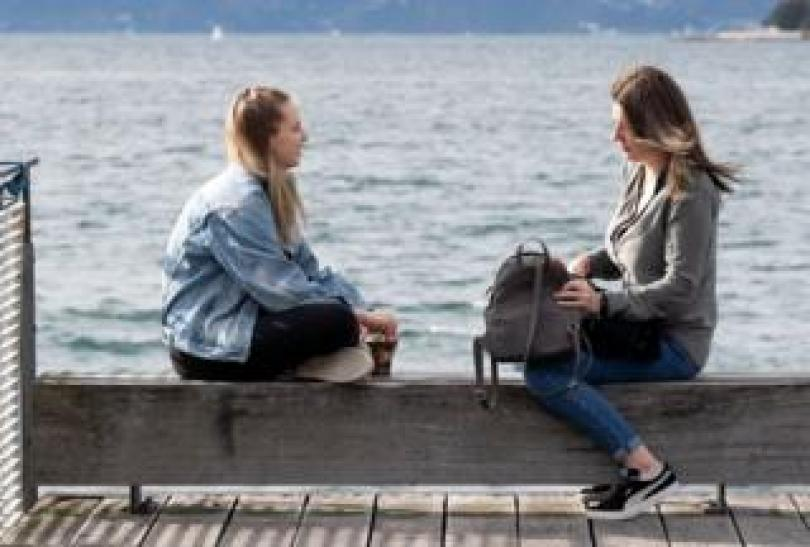 Women sit on the waterfront in Wellington on May 14, 2020.