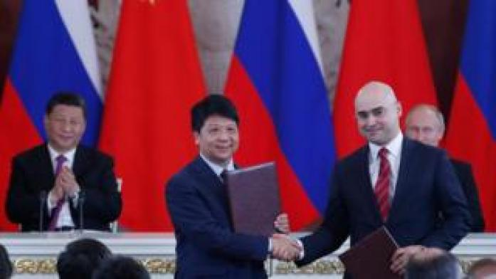Chinese President Xi Jinping (L) and Russian President Vladimir Putin (R) applaud as Guo Ping (2L), Deputy Chairman of the Board and Rotating Chairman of Huawei, shakes hands with Alexei Kornya (2R), President and CEO of Russian mobile phone operator MTS, during a signing ceremony following Russian-Chinese talks at the Kremlin in Moscow on June 5, 2019.